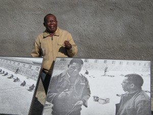 A guide explains the experiences of Nelson Mandela and Walter Sisulu (left and right in the poster) at Robben Island prison. Photo by Barbara Borst