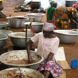 Members of a women's cooperative in Tamale work in groups on the long process of extracting shea butter, an ingredient used in cosmetics and food production.