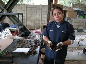 Alma Vasquez of FAFG explains signs of violent death on bones at La Verbena cemetery. Photo by Barbara Borst