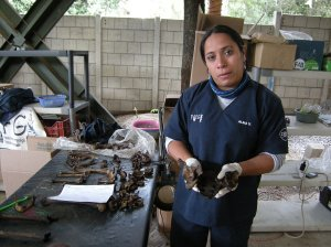 Alma Vasquez of FAFG explains signs of violent death on bones at La Verbena cemetery. Photo by Barbara Borst