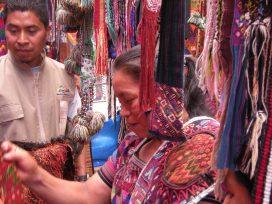 A guide and a vendor look through Maya weavings.