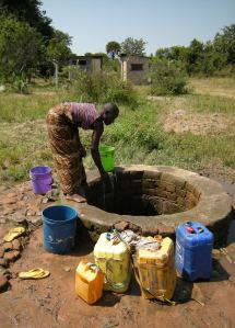 A girl called Happiness draws water from the one free well in Ulyankulu, Tanzania. Photos by Barbara Borst