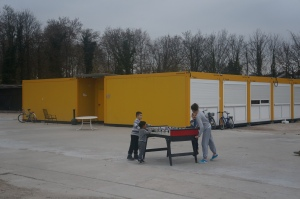 Children play foosball outside the containers that house asylum-seekers in a refugee camp at Linkenheim, Germany. Photo by Kavitha Surana